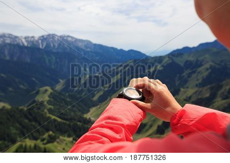 successful woman hiker checking the altimeter mountain top