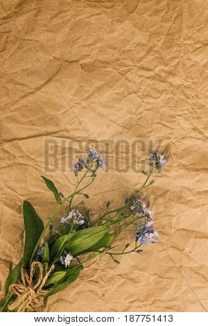 A Bouquet Of Blue Forget-me-not Flowers On An Old Yellow Rumpled Parchment Paper. View From Above.
