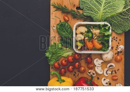 Healthy vegetarian food delivery background. Fresh organic vegetables on black. Natural food in foil box and wooden cutting board with copy space.