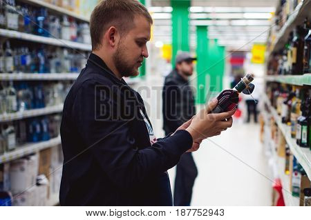 Bearded Man, In A Black Jacket, Stopped To Make My Choice In Store Window, Holds A Bottle Of Strong