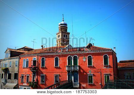 Colorful residential buildings and campanile of church San Pietro Martire in Burano island, Venice lagoon .