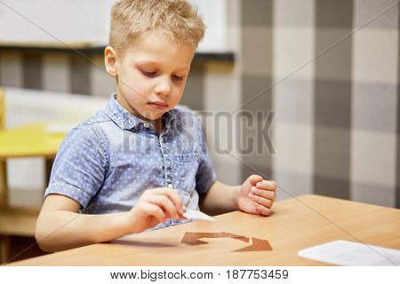 Little boy solves puzzle sitting at desk in room.