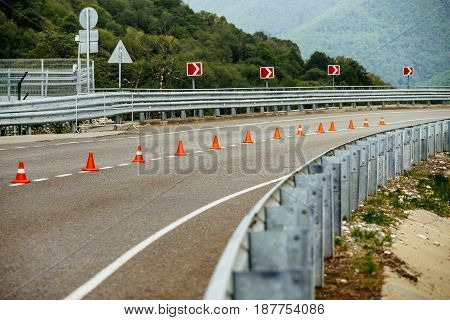 serpentine mountain roads with traffic cones safety and guardrail