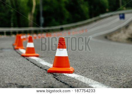 bright orange traffic cones on dark asphalt serpentine mountain roads