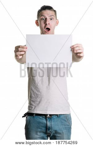 Young Handsome Guy With A Blank Sheet Of Paper, Looking Surprised Shot. Place For Signature, Text. V