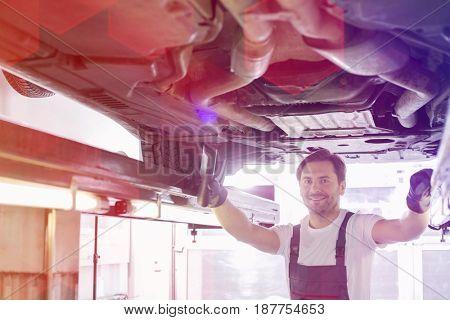 Portrait of smiling repair worker examining car in workshop