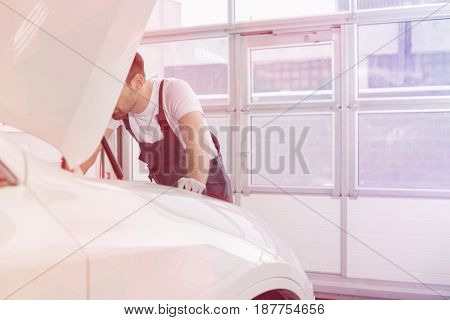 Midsection of male technician repairing car engine in workshop