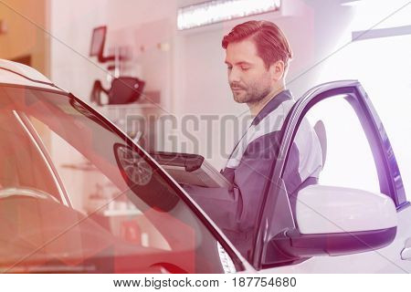 Side view of male maintenance engineer holding tablet PC while examining car in workshop