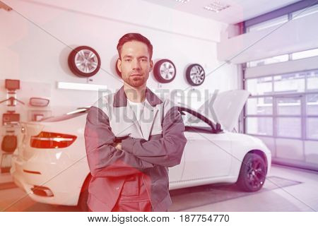 Portrait of confident male automobile mechanic standing in front of car at workshop