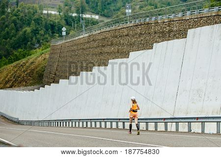 young woman athlete in compression socks running downhill
