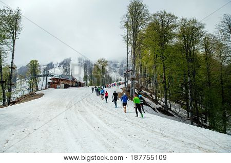 group runners running one after another snow mountain trail