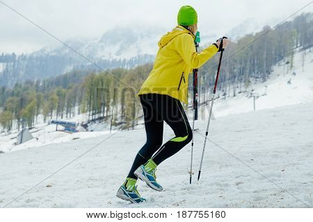 female runner with trekking poles on background snowy mountains