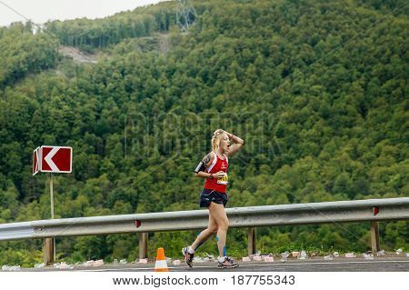 Rosa Khutor Russia - May 7 2017: young woman runner on water point in hand sponge with water in race Spring mountain marathon