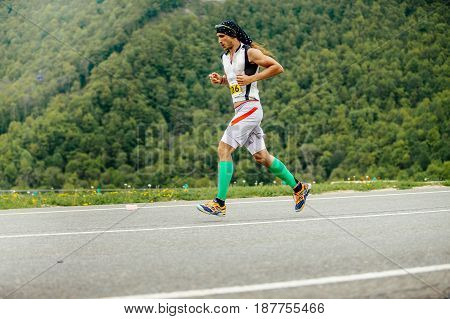 Rosa Khutor Russia - May 7 2017: male runner running in compression socks on background of mountains and green trees in race Spring mountain marathon