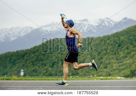 Rosa Khutor Russia - May 7 2017: man runner on water point pours face from water bottle in race Spring mountain marathon
