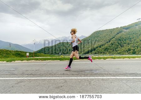 Rosa Khutor Russia - May 7 2017: woman runner running in compression socks on asphalt road in race Spring mountain marathon