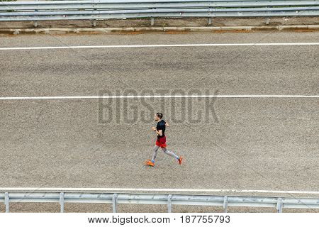 Rosa Khutor Russia - May 7 2017: side view of male runner running on dark asphalt road in race Spring mountain marathon