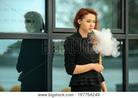 Vape Teenager. Young Pretty White Girl With Red Curly Hair And Modern Haircut In Black Dress Vaping