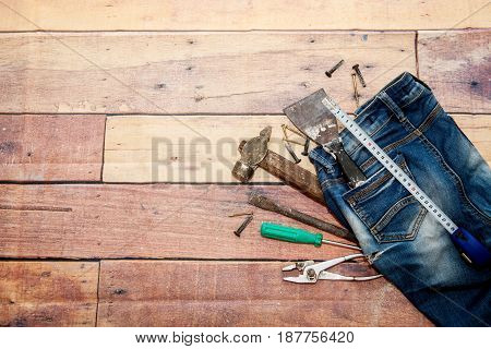 Tools hammer, screwdriver and nails are lying on old jeans on a wooden background. Repair and construction