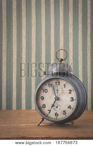 The old alarm clock is on the table on the background of striped wallpaper