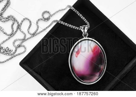 Pink agate medallion on silver chain in jewel box closeup