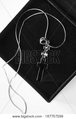 Black metal cross on silver chain in jewel box closeup