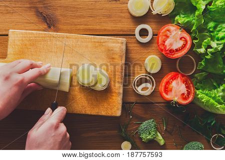 Cooking healthy food background. Cutting leek, fresh organic vegetables on wood. Natural food with copy space.