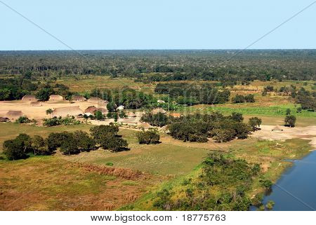 Aerial of traditional Amazon Indian village with houses in circle near Xingu River in Brazil