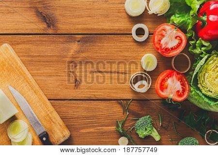 Cooking healthy food background. Cutting leek, fresh organic vegetables on wood with copy space. Natural food with copy space.