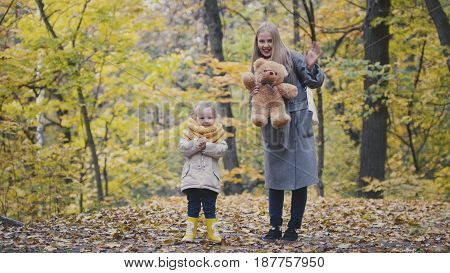 Little daughter with her mother and Teddy Bear walking in autumn park, telephoto