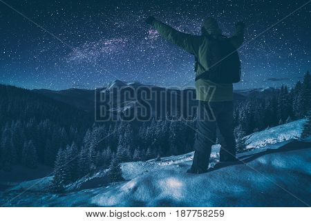 Hiker standing with raised hands against starry night sky with milky way above the winter mountain valley. Instagram stylisation.