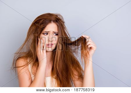 Sad Young Cute Girl Is Looking At Her Damaged Hair With Shock, Standing Isolated On A Pure Backgroun