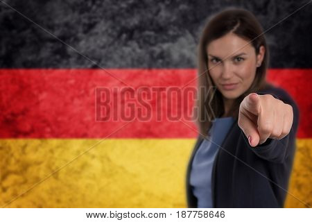 Beautiful Businesswoman Pointing Her Finger At You German Flag Background.