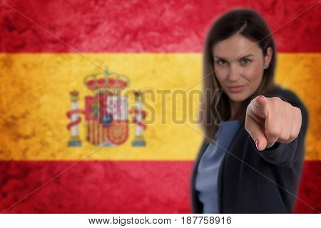 Beautiful Businesswoman Pointing Her Finger At You Spain Flag Background.