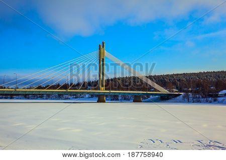 Snowy winter in the Arctic, Rovaniemi. Magnificent String Bridge through the frozen river of Kemijoki