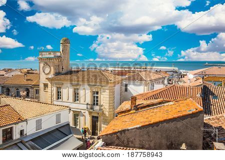 Yellow and orange tiled roofs and Mediterranean Sea. Morning gypsy carnival in a picturesque Provencal city Saintes-Maries-de-la-Mer. The concept of ethnographic tourism