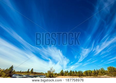 Cirrus clouds and strong wind.  Old Pinawa Dam Provincial Heritage Park, Canada. Warm autumn day.  The concept of ecological and recreational tourism