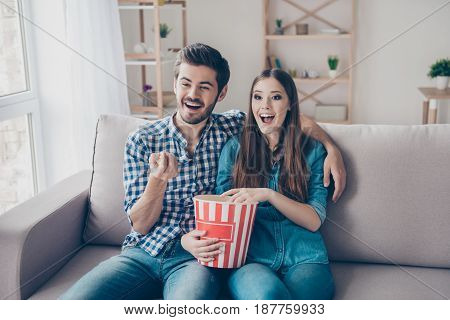 Young Beautiful Couple Is Watching Movie Indoors At Home, Eating Popcorn From A Box And Watching Com