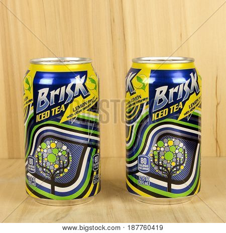 RIVER FALLS,WISCONSIN-MAY 22,2017: Two cans of Brisk brand iced tea with a wood background.
