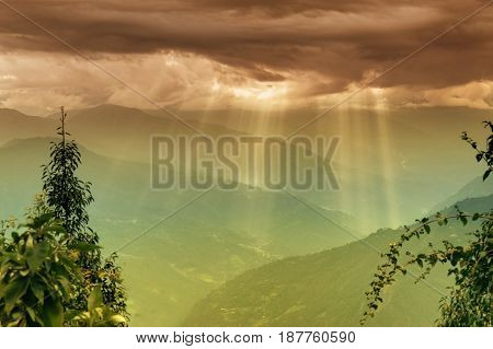 Sun rays coming out of cloud burst - at Rabangla Sikkim India. Trees in foreground and Himalayan mountains in background.