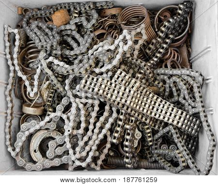 A selection of bicycle chains and some springs in a box