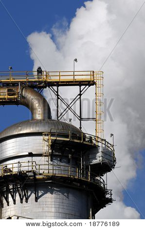 Closeup of smoke rising behind a distillation tower at a petrochemical plant