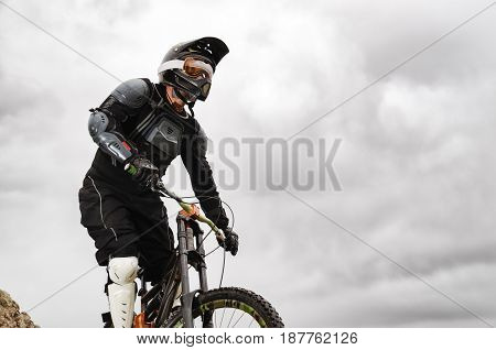 Professional Downhill rider on a mountain bike ride along the hill against the backdrop of the mountain range and the approaching storm at sunset Extreme Sport Concept.