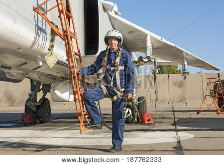 Military Pilot In Helmet Stands Near Jet Plane