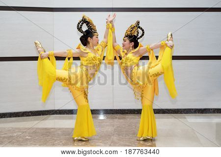 two beautiful girl actress in yellow traditional chinese stage costumes standing in acrobatic pose with one leg up