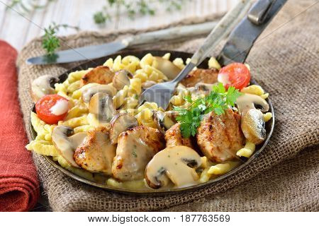Fried medallions of pork fillet with Swabian spaetzle (so called Schwabenpfandl or Schwabentopf ) and mushroom cream sauce served in an iron frying pan on a rustic table with an old jute sack