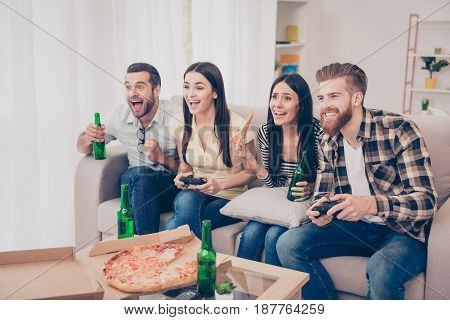 Four Friends, Fans Of Games, Sitting At The Sofa In Nice Cozy Home, Playing Video Game And Showing E
