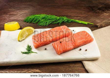 Two slices of salmon on a dark background with a place for text, with slices of lemon, peppercorns, and dill sprigs, with a place for text