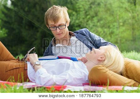 Young Attractive European Couple With Small Dog Is Getting Rest On Blanket In Some Summer Park At Wa