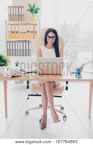 Portrait Of Charming Young Brunette Businesswoman In Stylish Glasses And Strict White Dress, Sitting